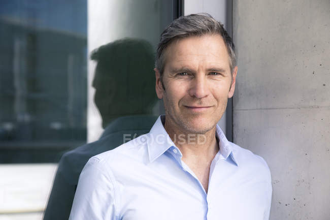 Portrait of confident mature businessman at a glass front — Stock Photo