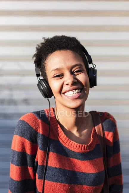 Retrato de rir jovem ouvindo música com fones de ouvido — Fotografia de Stock