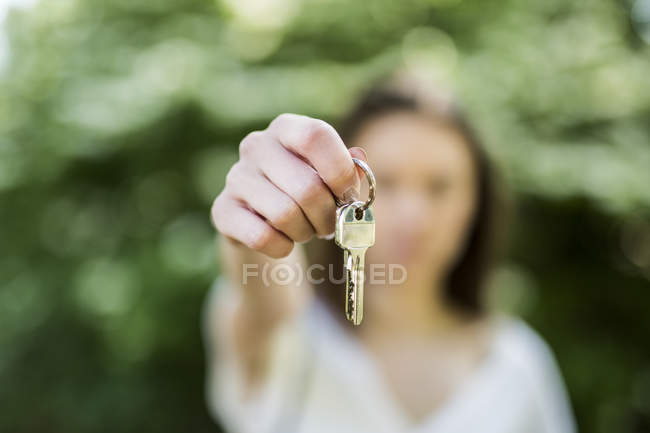 Close-up of woman holding key outdoors — Stock Photo