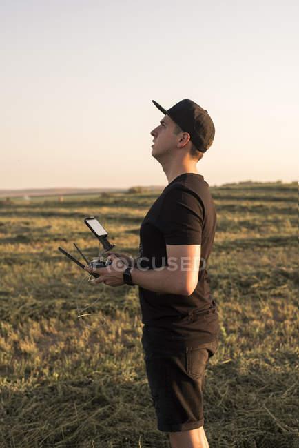 Uomo con telecomando per drone in un campo — Foto stock