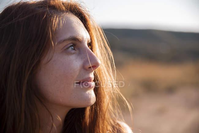 Sorridente giovane donna con lentiggini guardando altrove — Foto stock
