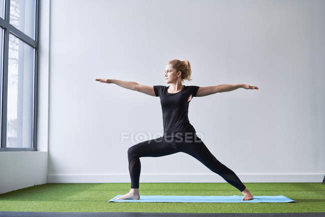 Woman doing yoga exercise in studio — Stock Photo