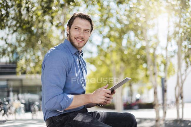 Uomo d'affari sorridente utilizzando tablet all'aperto nella natura — Foto stock