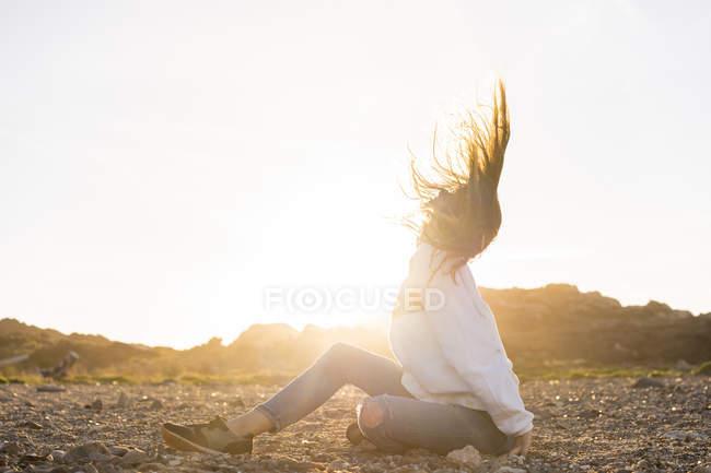 Giovane donna in spiaggia, gettando i capelli al tramonto — Foto stock