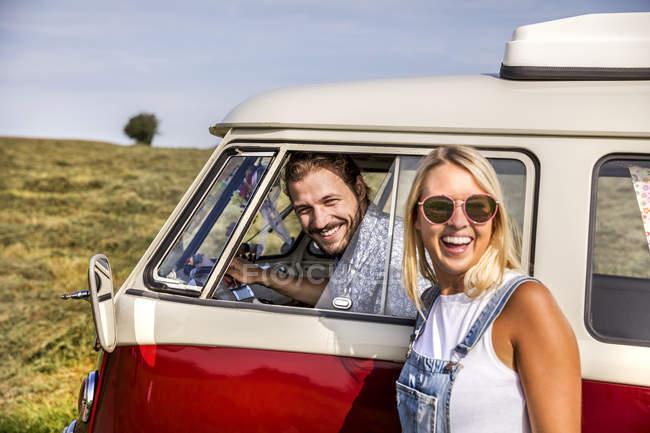 Счастливая пара с фургоном в сельской местности — стоковое фото