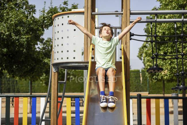Petite fille s'amuser sur la glissière sur l'aire de jeux — Photo de stock