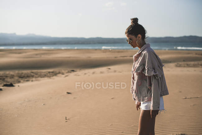 Fashionable teenage girl in jacket and shorts on sandy beach — Stock Photo