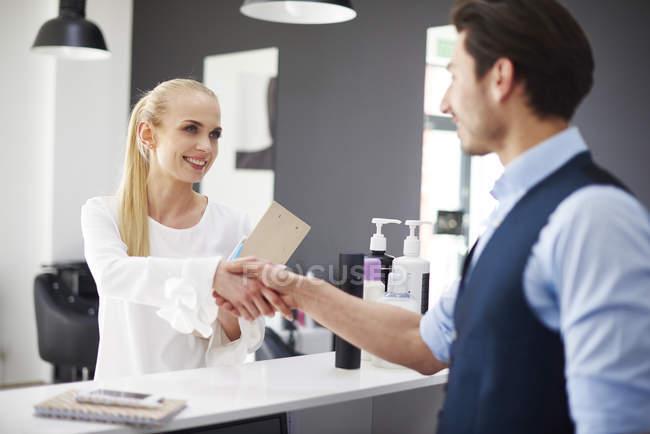 Парикмахер и улыбающаяся женщина пожимают руки в парикмахерской — стоковое фото
