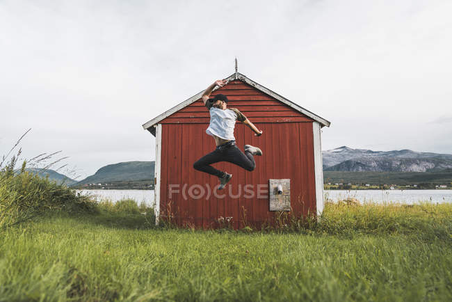 Giovane che salta davanti al fienile rosso in Norvegia — Foto stock