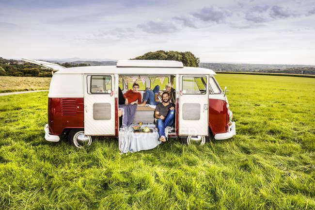 Amis pique-nique dans une camionnette garée sur le terrain dans un paysage rural — Photo de stock