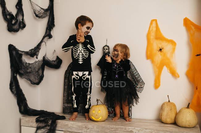 Garçon et petite sœur en costumes effrayants Fête de l'Halloween — Photo de stock