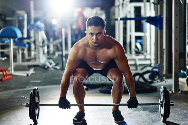 Человек поднимает штангу в тренажерном зале — стоковое фото