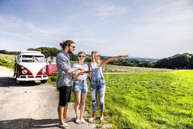 Друзья с планшетом снаружи фургона в сельской местности — стоковое фото