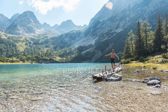 Austria, Tyrol, Young man at Lake Seebensee balancing on tree trunk — Stock Photo