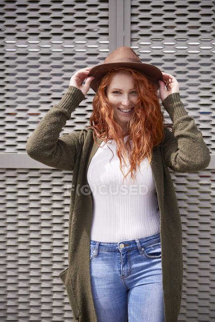 Portrait of smiling redheaded woman with brown hat — Stockfoto