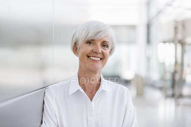 Portrait of smiling senior businesswoman leaning on wall — Stock Photo