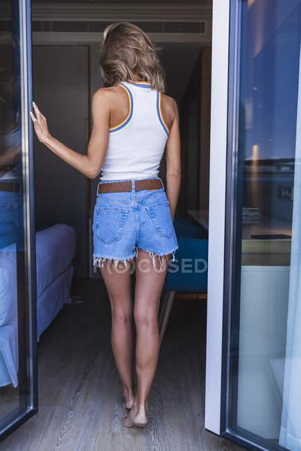 Visão traseira da jovem mulher deixando varanda — Fotografia de Stock