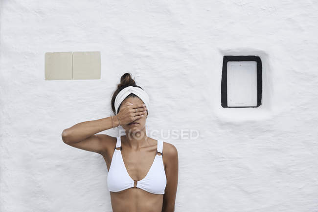 Young woman wearing white bikini top leaning against white wall and covering eyes with hand — Stock Photo