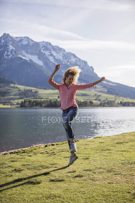 Австрія, Тіроль, Вальчзе, щаслива жінка, що стрибає на озеро. — стокове фото