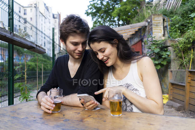 Young couple at outdoor bar with beer and cell phone — Stock Photo