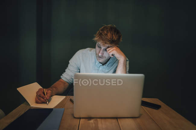 Mann sitzt im Büro, arbeitet spät in seinem Start-up-Unternehmen und macht sich Notizen — Stockfoto