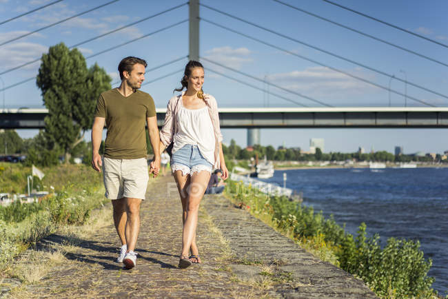 Happy couple walking hand in hand on waterfront promenade in summer — Stock Photo