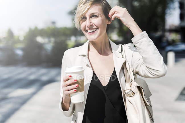 Porträt einer lachenden Geschäftsfrau mit Kaffee zum Spazierengehen — Stockfoto