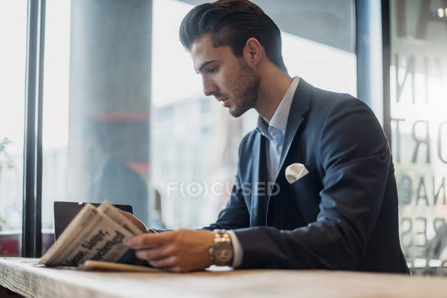 Young businessman reading newspaper in a cafe — Stock Photo