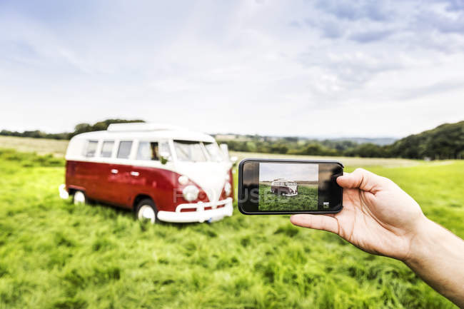 Woman's hand taking cell phone picture of van in rural landscape — Stockfoto