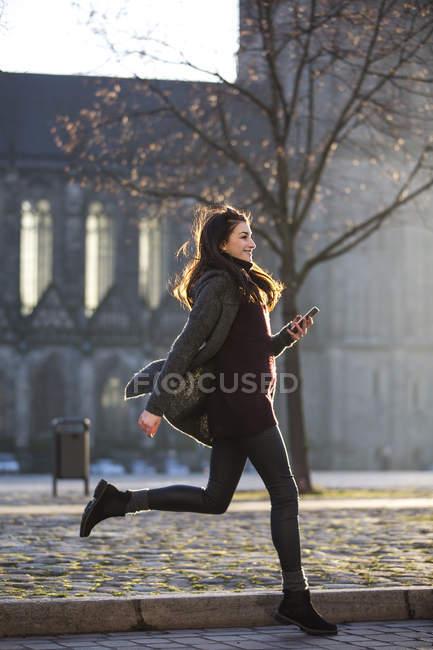Усміхнена молода жінка з стільниковий телефон перетину вулиці — стокове фото