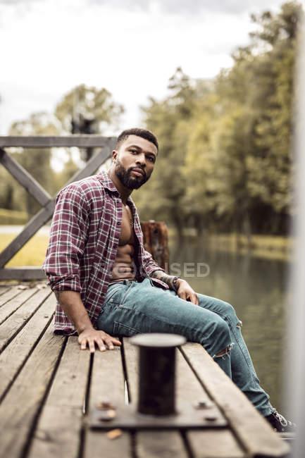 Retrato de homem musculoso sentado no molhe — Fotografia de Stock