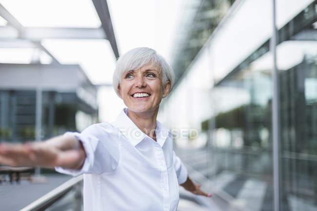 Felice donna anziana in città con le braccia tese — Foto stock