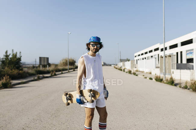Portrait of sportive man in white and blue with skateboard on empty gray paved road — Foto stock