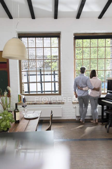 Mature couple standing in their comfortable loft, looking out of window, rear view — Stock Photo