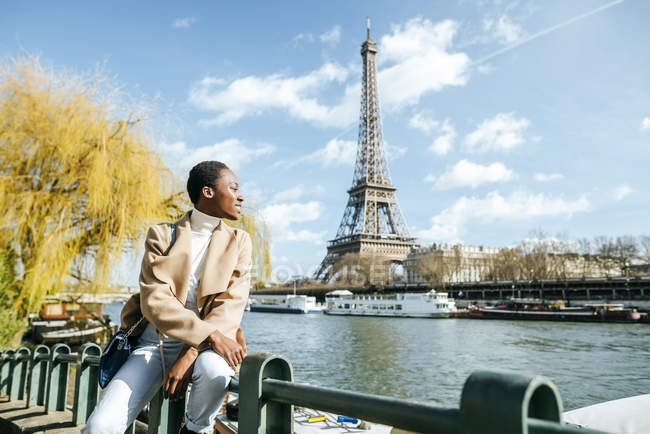 Francia, Parigi, Donna sorridente alla Senna con la Torre Eiffel sullo sfondo — Foto stock