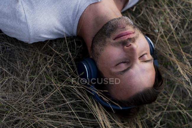Entspannter Mann, der auf dem Feld liegt und mit Kopfhörern Musik hört — Stockfoto