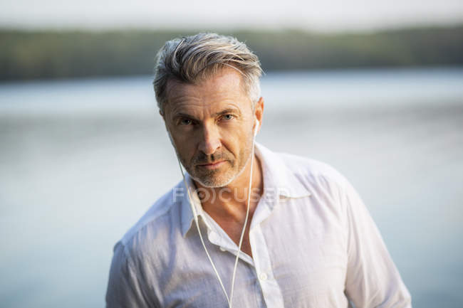Portrait of mature man with earphones at lake — Stock Photo