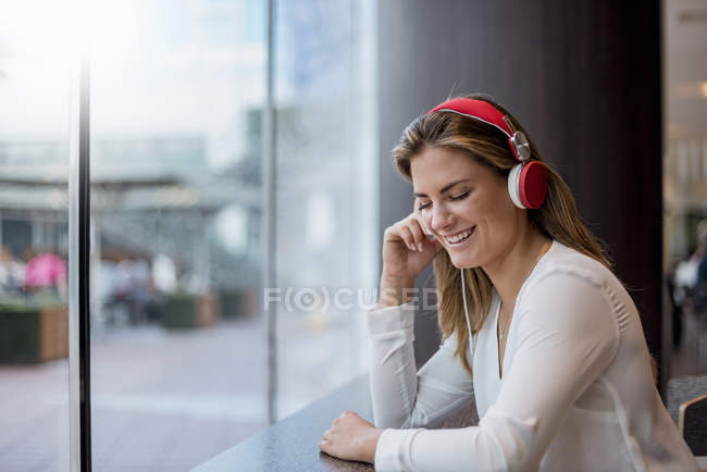 Joyeux jeune femme écoutant de la musique avec des écouteurs — Photo de stock