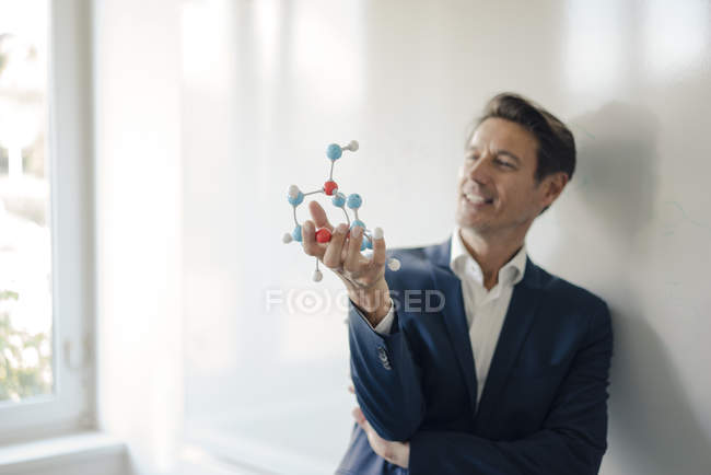 Successful businessman leaning on whiteboard, holding molecule model — Stock Photo
