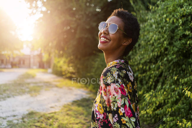 Felice giovane donna che indossa occhiali da sole all'aperto al tramonto — Foto stock