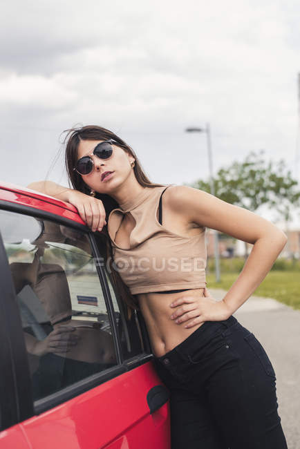 Retrato de mujer joven con gafas de sol apoyadas en el coche - foto de stock