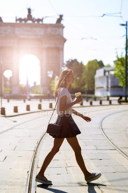 Italia, Milán, mujer joven caminando en la ciudad soleada - foto de stock
