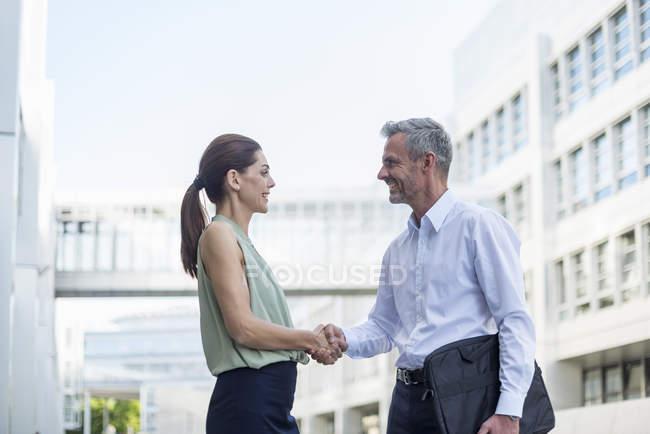 Бізнес - партнери потискуються просто неба. — стокове фото