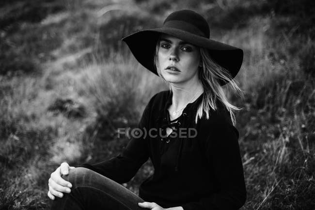 Portrait of young woman wearing black hat and sitting outdoors and posing on camera — Stock Photo