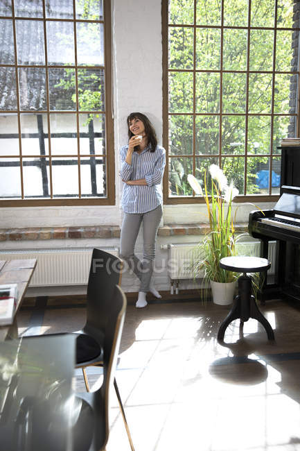 Woman standing at window of her loft apartment, drinking coffee — Stock Photo