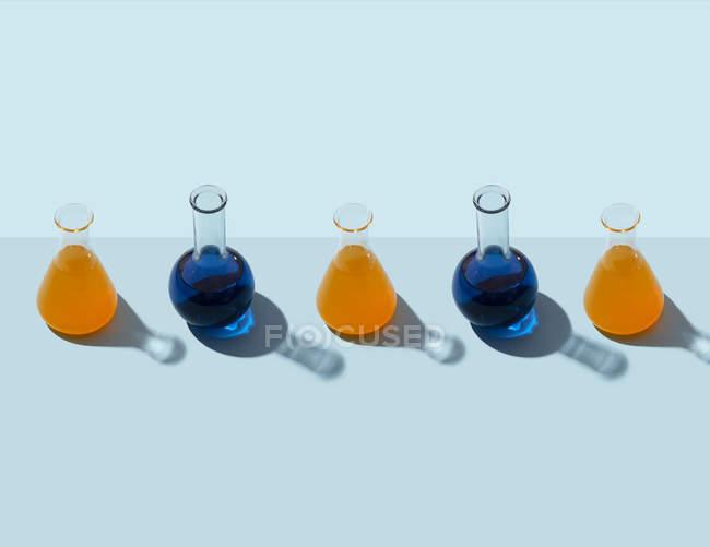 Fila de tubos de ensayo con líquido azul, fondo azul claro - foto de stock