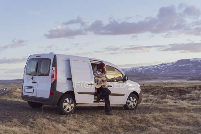 Ісландія, молода людина, спираючись на Ван і грати на гітарі — стокове фото
