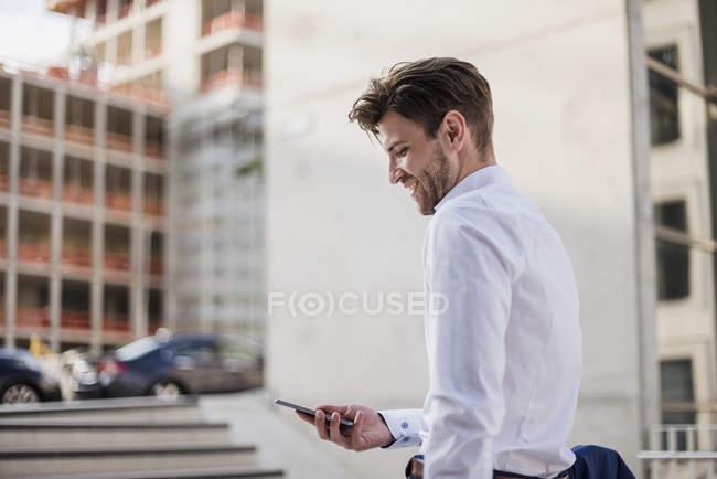 Geschäftsmann steht in der Stadt und benutzt Handy — Stockfoto