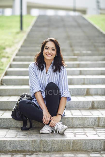 Retrato de estudiante sonriente sentado en escaleras al aire libre - foto de stock