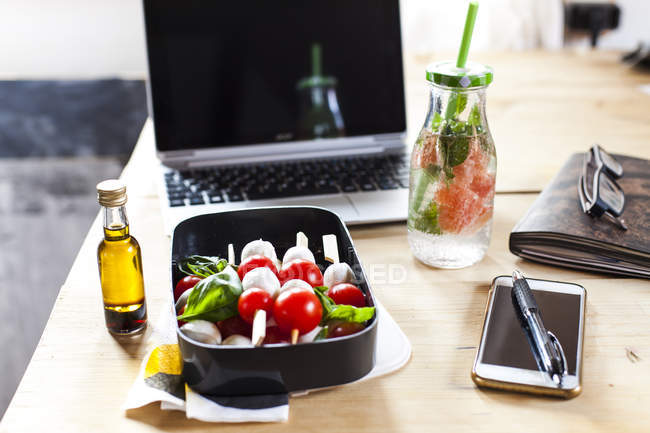 Lunch box of Caprese salad, bottle of infused water and laptop on desk — Stock Photo